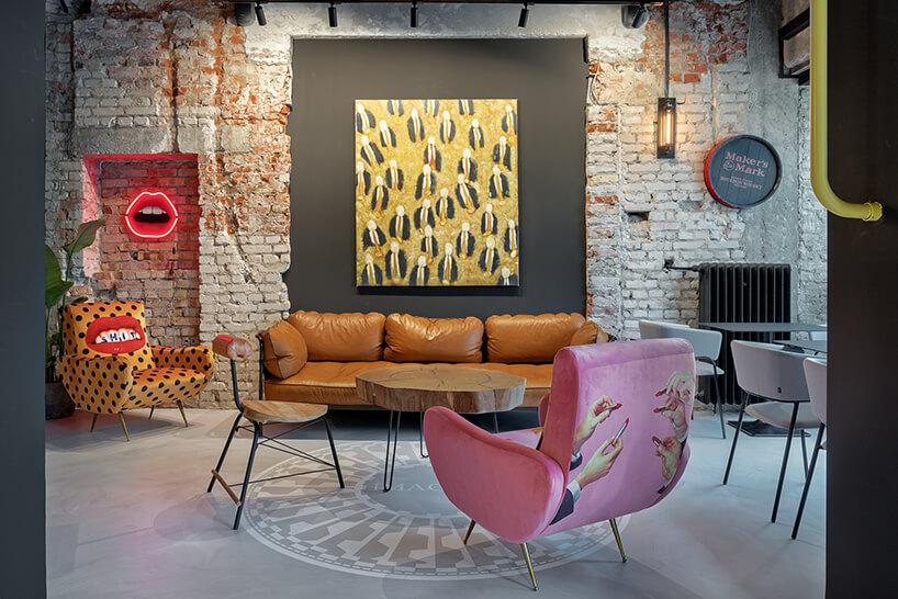 wnętrze restauracji POP in projektu Sikora Wnętrza różowy fotel na tle brązowej sofy iobrazu na szarej ścianie