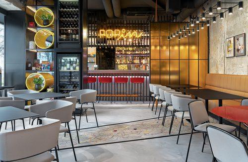 wnętrze restauracji POP in projektu Sikora Wnętrza czarne stoliki z szarymi krzesłami na tle baru z neonem POPin