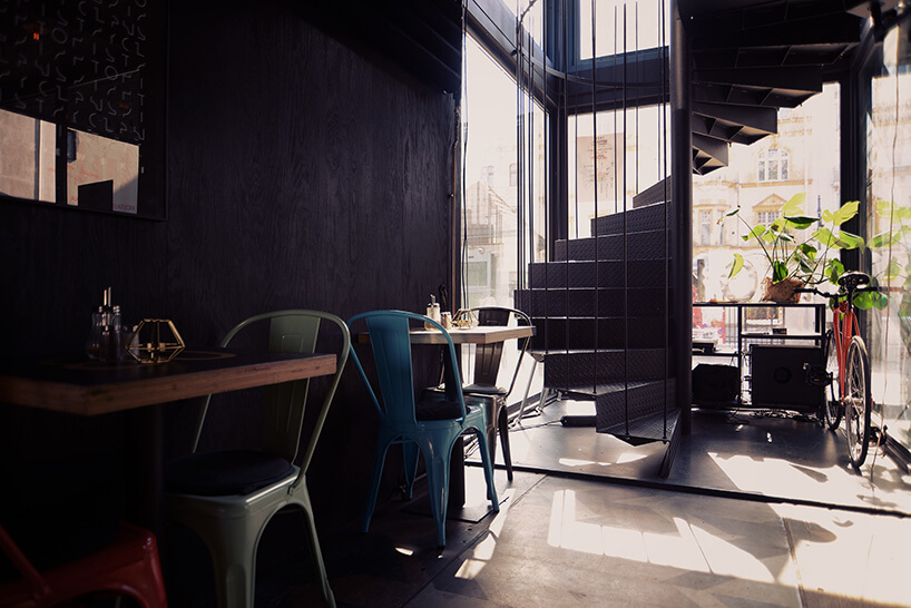 dwuosobowe stoliki obok kręconych schodów