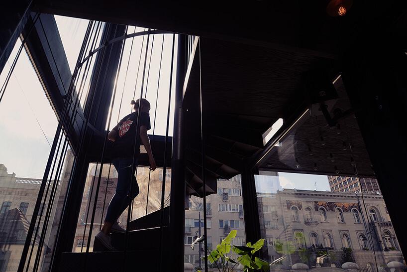 kobieta wchodząca po kręconych metalowych schodach