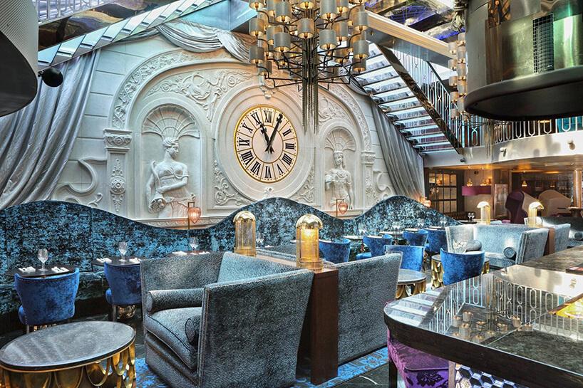 wnętrze restauracji Le Pain Francais projektu wniebieskich odcieniach idużym zegarem na głównej ścianie