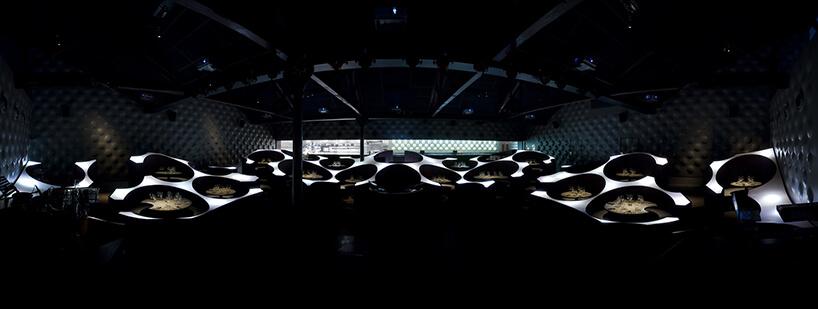 nowoczesne wnętrze restauracji Blue FROG projektu Serie Architects zpodświetlonymi stolikami