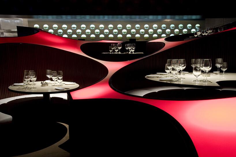 nowoczesne wnętrze restauracji Blue FROG projektu Serie Architects zpodświetlonymi stolikami rozdzielone czerwonymi panelami
