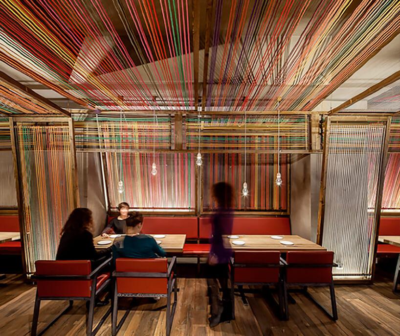 proste wnętrze restauracji ze ścianami isufitem zkolorowych nitek