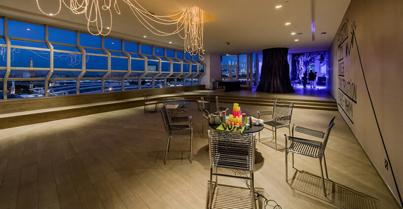 przestronne wnętrze restauracji zdwoma stolikami na tle panoramy miasta nocą