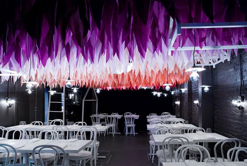 czarne wnętrze restauracji zbiałymi stolikami ikrzesłami pod zwisającymi kolorowymi skrawkami materiału