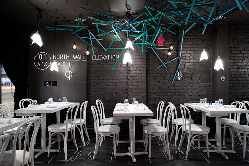 czarne wnętrze restauracji zbiałymi stolikami ikrzesłami pod zielonymi iniebieskim prętami na suficie iścianie