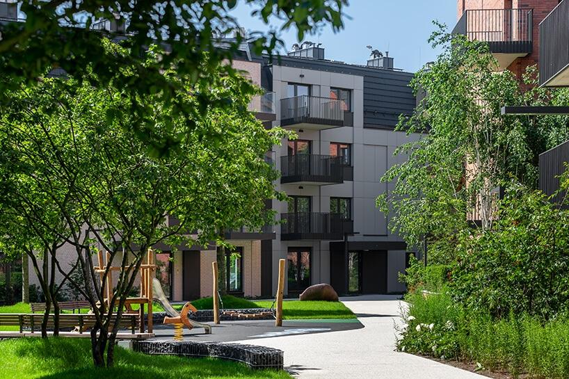 nowoczesne osiedle zdużą ilością drzew izielenie przy szarym budynku
