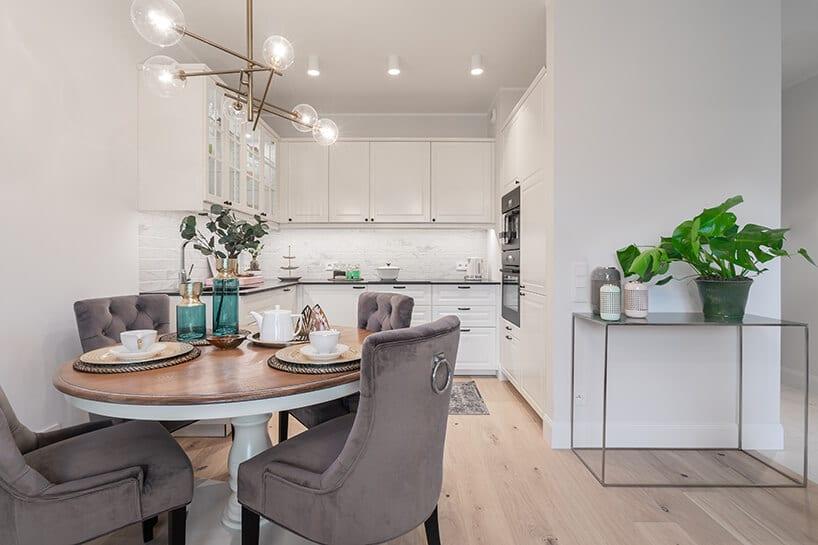 biały stół na pojedyńczej nodze przy białej kuchni wmieszkaniu