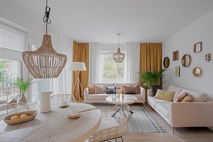 dwie kanapy wkolorze pudrowego różu zszarymi poduszkami wsalonie zpomarańczowo-złotymi zasłonami