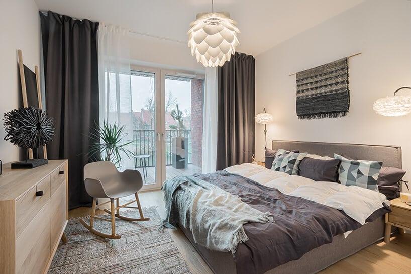 sypialnia zdodatkami iłóżkiem wkolorze szarym adodatkowo fotel bujany