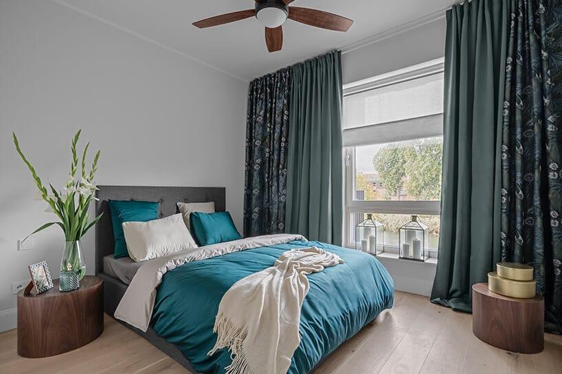 sypialnia zdodatkami wkolorze niebieskim oraz zielonym izasłonami wkwiaty