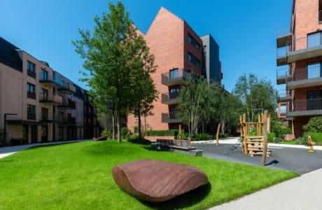 małe bloki z cegły ze spadzistym dachem na osiedlu z dużą ilością zieleni