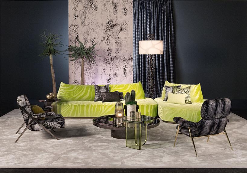 zielonkawa sofa wśrodku pomieszczenia oczarnych barwach