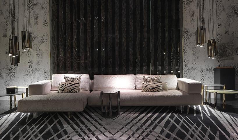 beżowa ogromna sofa zpoduszkami na tle wzorzystej ściany
