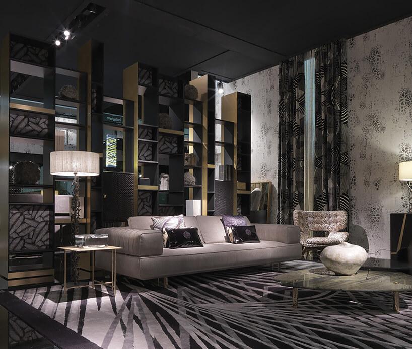 nowoczesna ścianka zpólek na wróżnych rozmiarach obok kanapy postawionej na dywanie