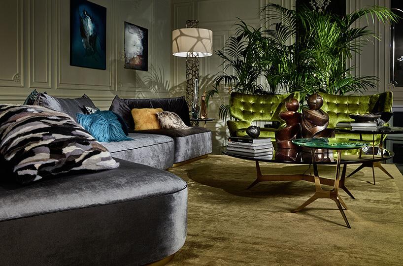 wnętrze salonu roberto canavali zdużą sofą wszarych barwach idodatkami zieleni