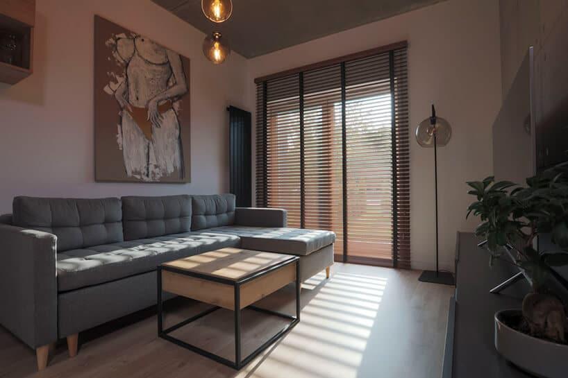 pomieszczenie zszarą pikowaną kanapą ibeżowymi ścianami zdużym oknem inowoczesną roletą zdrewnianymi listwami