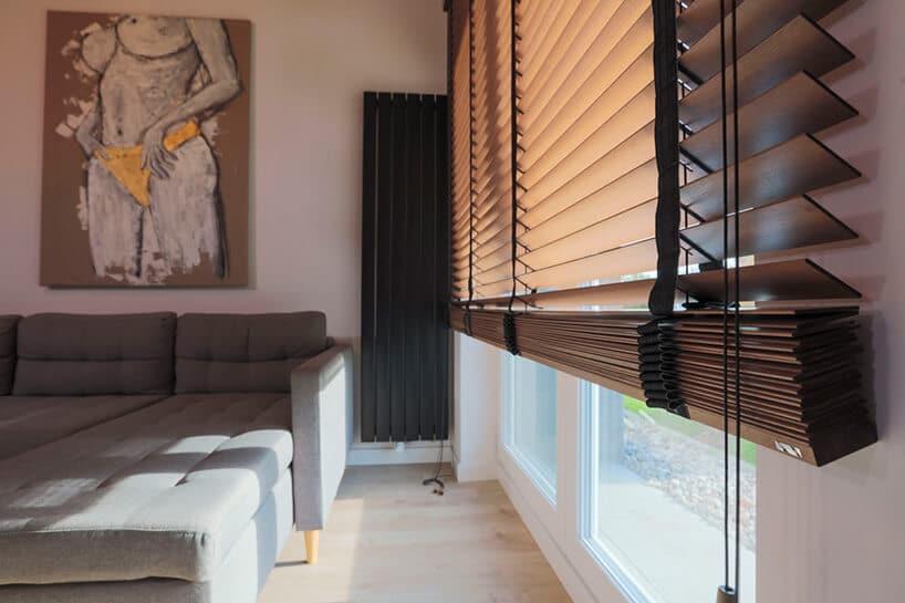 roleta na duże okno zdrewnianych listków iciemno szarego materiału wsalonie