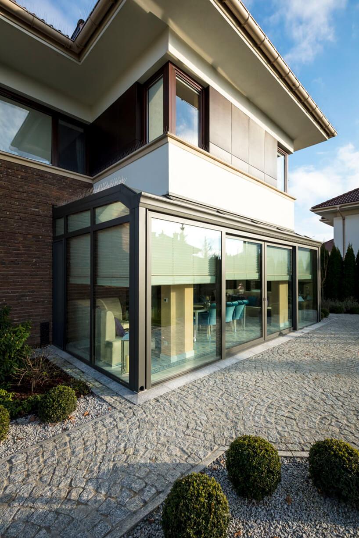nowoczesny dom kwadratowy zpiętrem oraz dużym przeszkleniem zwitrynami wkolorze ciemno szarym