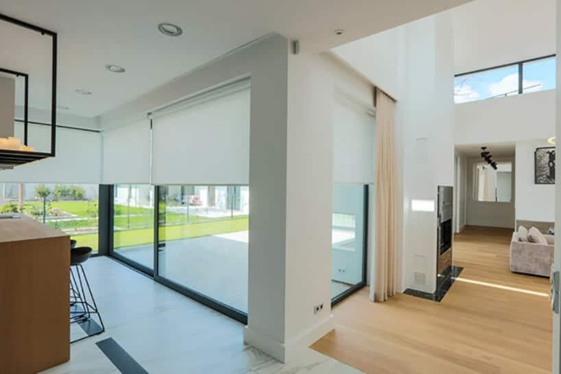 korytarz wnowoczesnym budownictwie zdużymi witrynami oraz roletami wkolorze białym zelektryką