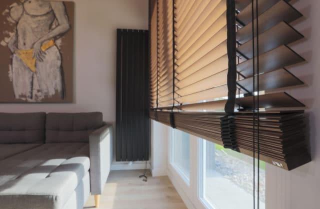 roleta na duże okno z drewnianych listków i ciemno szarego materiału w salonie