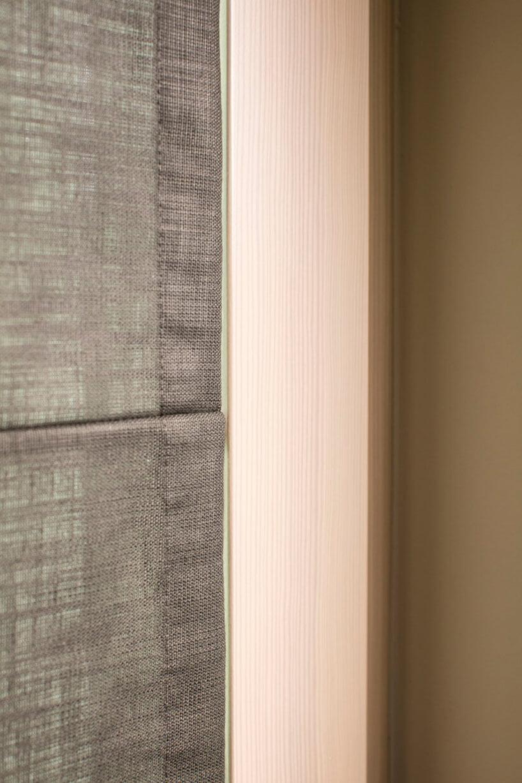 szare rolety rzymskie od Anwis wdrewnianym oknie zbliska