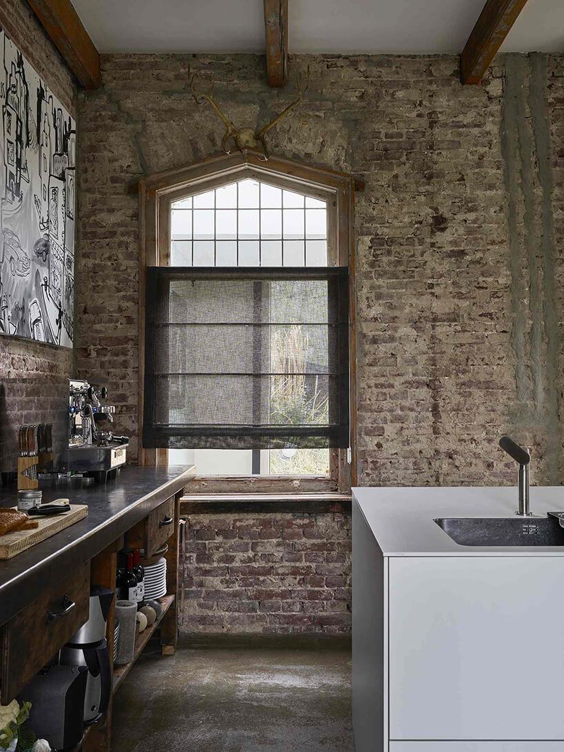 ciemna roleta rzymska od Anwis wdużym drewnianym oknie wceglanym lofcie