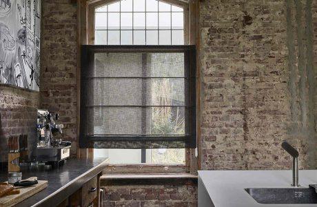 ciemna roleta rzymska od Anwis w dużym drewnianym oknie w ceglanym lofcie