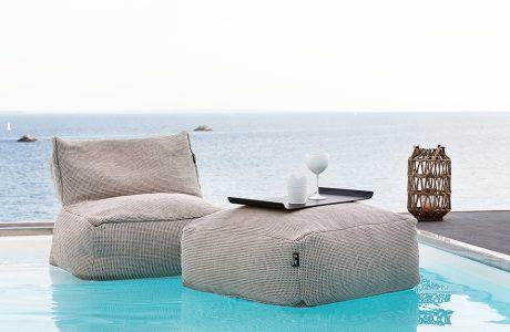 szara pufa i stolik materiałowy na powierzchni wody w basenie na tle tafli morza
