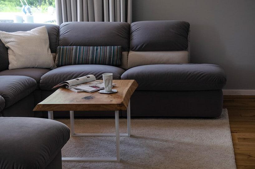 stolik kawowy zdębowego blatu na cienkich nogach przy dużej szarej kanapie