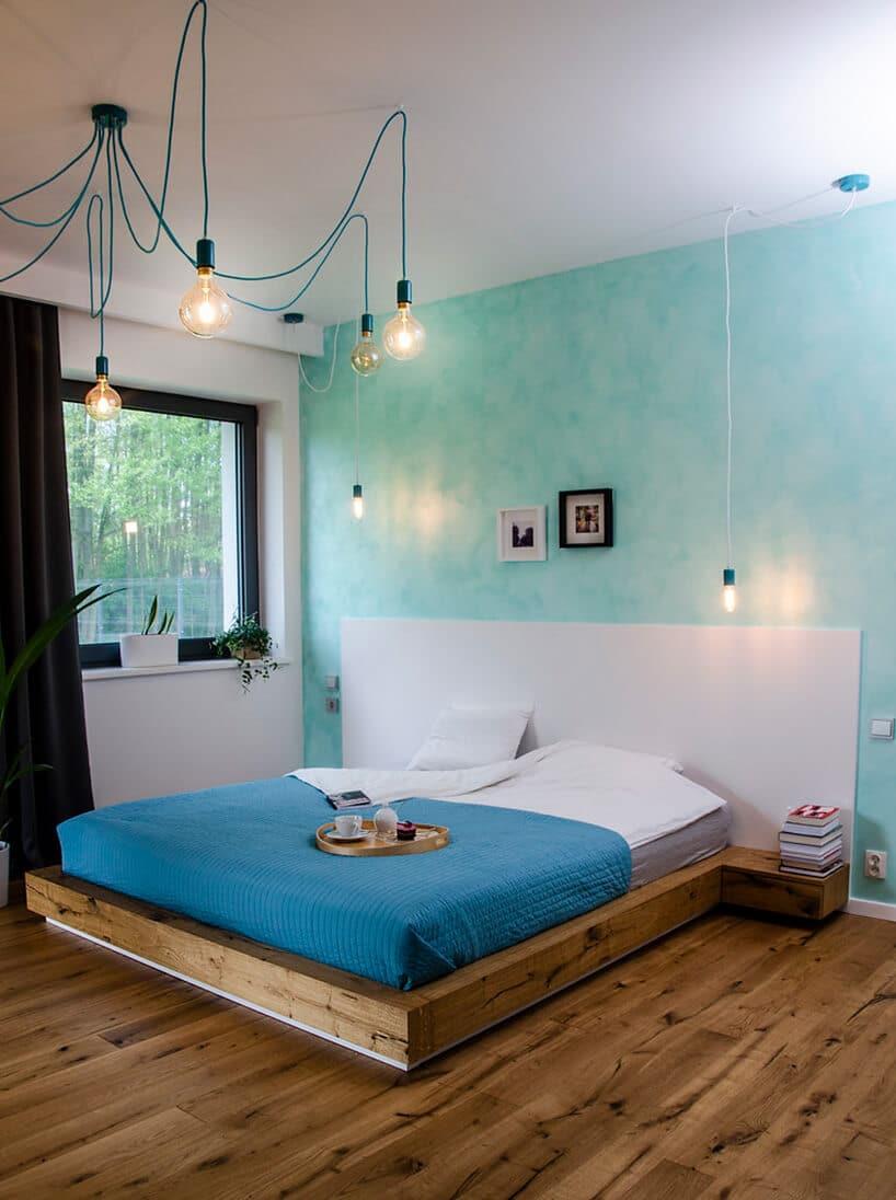 Drewniane łóżko wsypialni zjasno turkusową ścianą iwiszącymi żarówkami na kablu