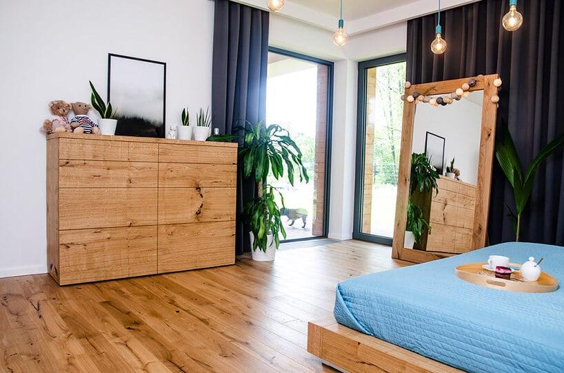 sypialnia zdębową komodą oraz drewnianą lakierowaną podłogą