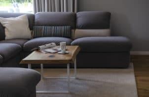 ciemna kanapa i drewniany stolik kawowy z dębu