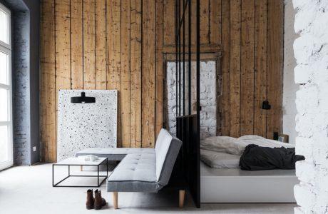 wnętrze pokoju z oddzieloną sypialnią od salonu na tle długich starych desek na ścianie