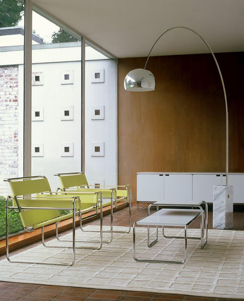 dwa zielone krzesła Wassily Chairs wprostym wnętrzu zprzeszkloną ścianą