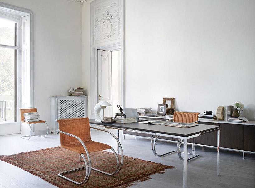 wyjątkowe krzesło MR Chair ztkanym brązowym siedziskiem ichromowanym stelażem przy eleganckim stole Knoll Table zczarnym blatem osadzonym na chromowanym stelażu