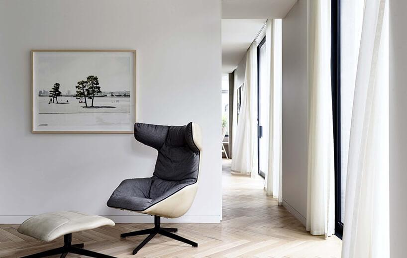 eleganckie krzesło Take aLine For aWalk od Moroso szare siedzisko zwysokim oparciem wykończone jasną skóra na zewnątrz na czarnych nogach