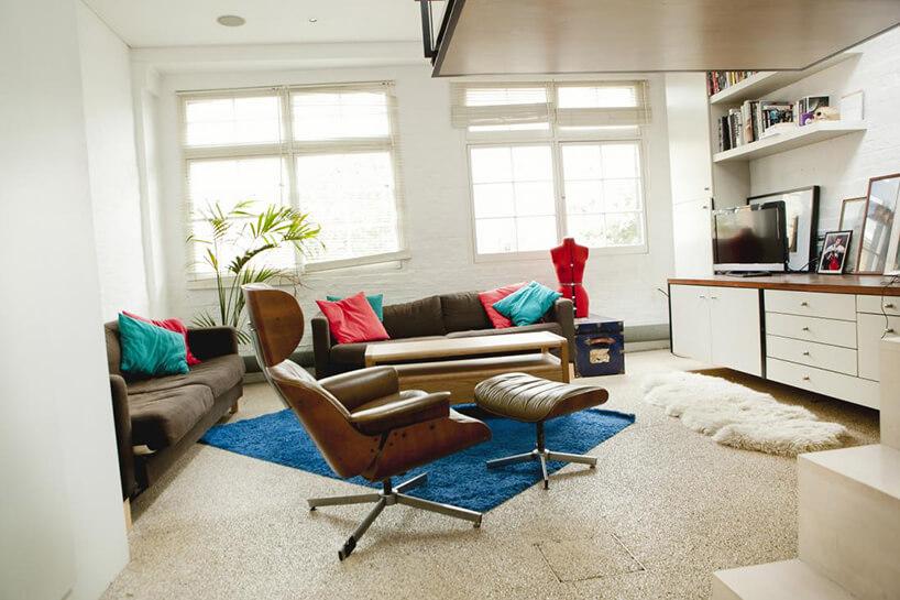 salon ze starym fotele zpodnóżkiem iciemnymi kanapami