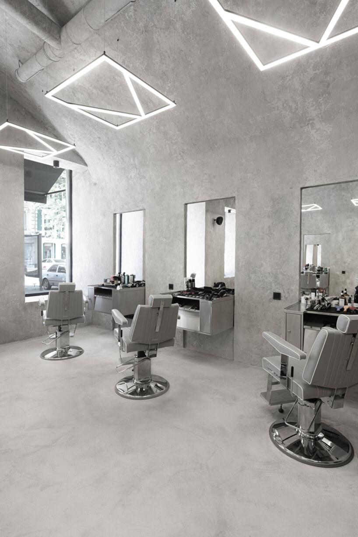 trzy szare fotele fryzjerskie wszarym wnętrzu zakładu fryzjerskiego