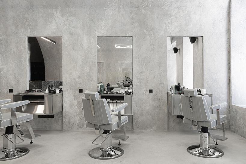 trzy stanowiska fryzjerskie zszarymi fotelami ilustrami wpuszczonymi wścianę