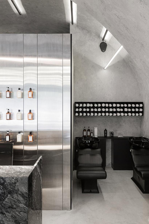 dwa czarne stanowiska do mycia głowy we wnęce obok ściany zpolerowanego metalu
