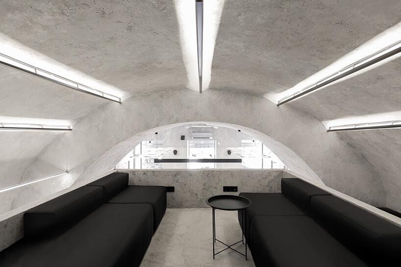 dwie czarne sofy pod owalnym betonowym sufitem