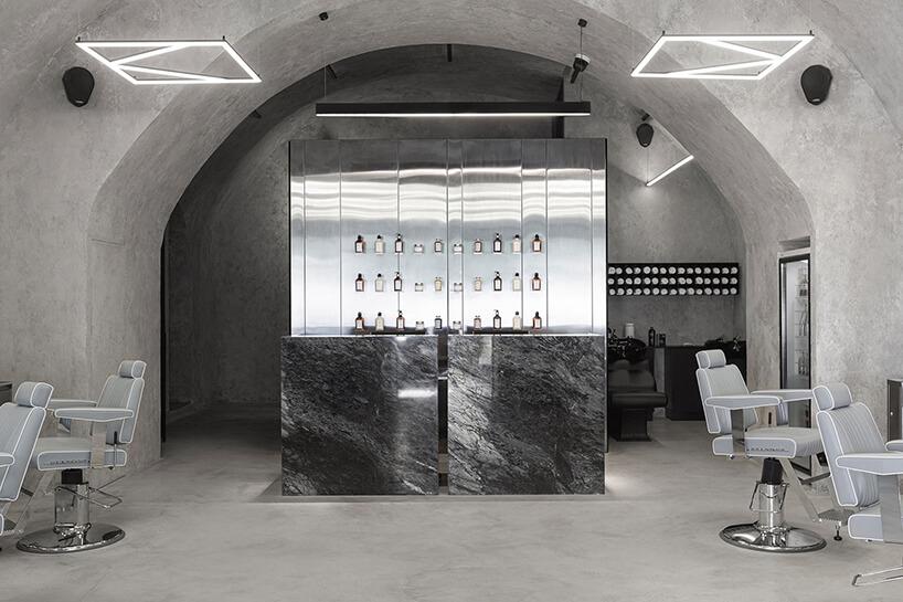 srebrne stoisko zblatem wykończonym ciemnym kamieniem na tle ściany zpolerowanego metalu
