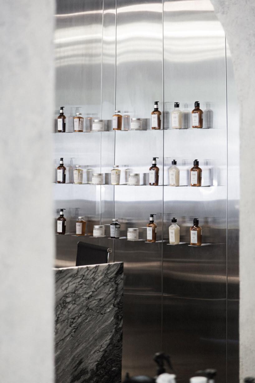 stoisko fryzjerskie zszary fotelem zbiałymi obszyciami metalowym wiszącymi stolikiem ilustrem wpuszczonym wścianę