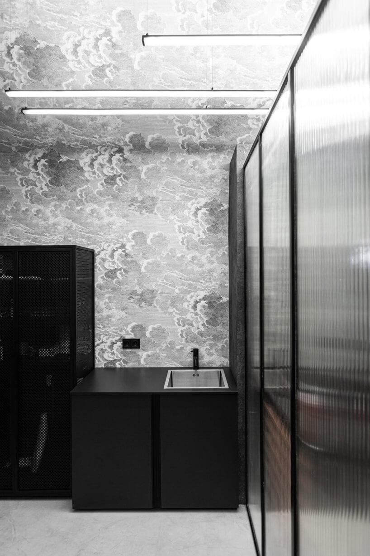 czarna szafka zumywalką za ścianką zplastiku na tle szarej ściany zmotywem chmur