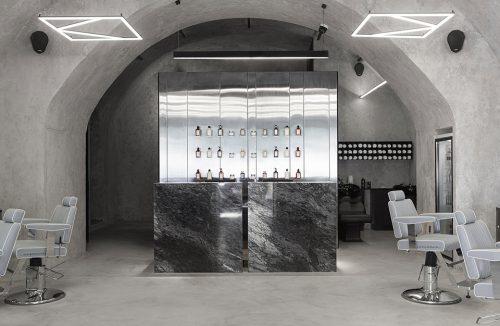 srebrne stoisko z blatem wykończonym ciemnym kamieniem na tle ściany z polerowanego metalu