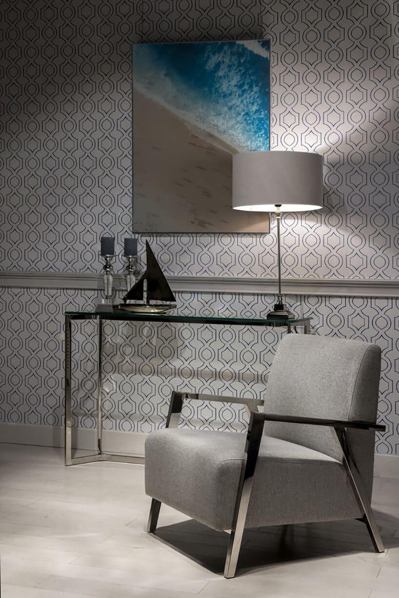 szary stylowy retro fotel zmetalową ramą wchromie na tle ściany zwzorami