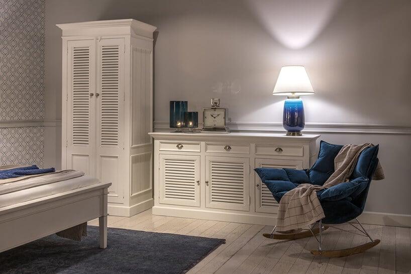 niebieski pikowany fotel bujany przy komodzie zkwadratowym zegarem zbiałą tarczą