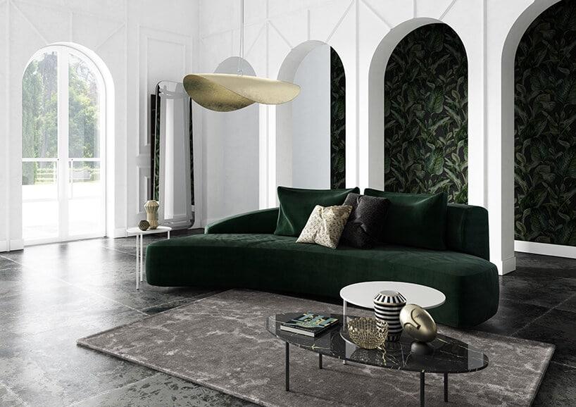 białe wnętrze zfilarami itapetą wmotywie liści oraz ciemno butelkowo zieloną kanapą